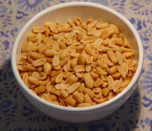 Barkeep shoves a bowl of peanuts...