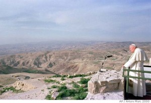 """Pope John Paul II stands on top of Mount Nebo, west of Amman, Jordan Monday March 20, 2000, where tradition says Moses first glimpsed the Promised Land. On the first papal pilgrimage to the Holy Land in 36 years, an emotional Pope John Paul II called Monday for a resolution of the region's """"grave and urgent"""" conflicts as he began a weeklong journey to retrace the footsteps of Jesus. (AP Photo/Arturo Mari - POOL)"""